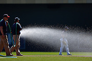 MINNEAPOLIS, MN - APRIL 14: Grounds crew sprays water toward a player while watering the infield before the game between the Texas Rangers and Minnesota Twins at Target Field on April 14, 2012 in Minneapolis, Minnesota. (Photo by Joe Robbins)