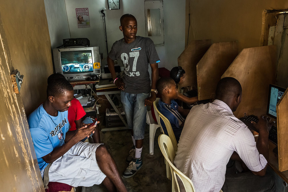"SABANETA DE YÁSICA - JUNE 28, 2015: John Presime, (center) is the Haitian owner of an internet café in the Cementerio neighborhood outside of Sabaneta. He snuck into the Dominican Republic a decade ago at age 14.  His best friend, is also named John,  John Tapia, (not pictured) and is a Dominican police officer, who will soon have to round up illegal Haitians for deportation. For the last year, Mr. Thomas has tried to convince his Haitian friends to register, passing them advice about which notary was cheapest, which registration centers had the shortest lines and which lawyers were honest.  But many could not complete all the needed steps, whether because of bureaucratic or financial hurdles. ""A lot of the Haitians who have paid fees but keep having to pay more and submit more documents feel like they are being robbed,"" he said, as Mr. Presime nodded in agreement.  That, it seems, is precisely what happened to Mr. Presime. Though he has a receipt, he has no formal documentation to prevent his deportation. And Mr. Tapia is left with an impossible choice, between his job and his friend.  PHOTO: Meridith Kohut for The New York Times"