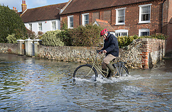 © Licensed to London News Pictures. 03/01/2018. Bosham, UK. A man cycles through tidal flood water at Bosham as storm Eleanor hits the south. Winds of up to 80 mph are being forecast today in parts of the UK. Photo credit: Peter Macdiarmid/LNP