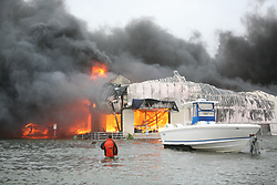 Stock photo of fire breaking out in a storm damaged structure on the water after Hurricane Ike