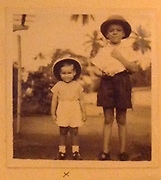 """David Meynert Collection.<br /> My elder brother Scott and me<br />       At the time we went to live in the<br />      Jungles at Palatupana.<br />     He has on a real """" Topi """" and I<br />     Have a soft false one.<br />     The latter better to fight with.<br />     Remember them!<br />     As I said before, mum used to let<br />     Us run around free in the jungles,<br />     With Robot ( Tracker's son about          <br />     The same age as my brother ) as if <br />     We were playing in the back  <br />     Streets of Colombo, completely<br />     Unaware that this was a survival <br />     Area for the wild animals."""