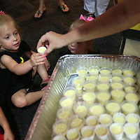 Elle Eads, 2, of Saltillo, reaches out for a smoothie from Jessie Leddy, Captain of the Universe Healthworks Team member, during Fun and Fit Friday on June 16. The camp is for children and their adult relatives where they have story time, crafts and an obstacle course in the Zoom Room.