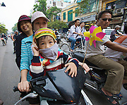 Girls with child on a motorbike.