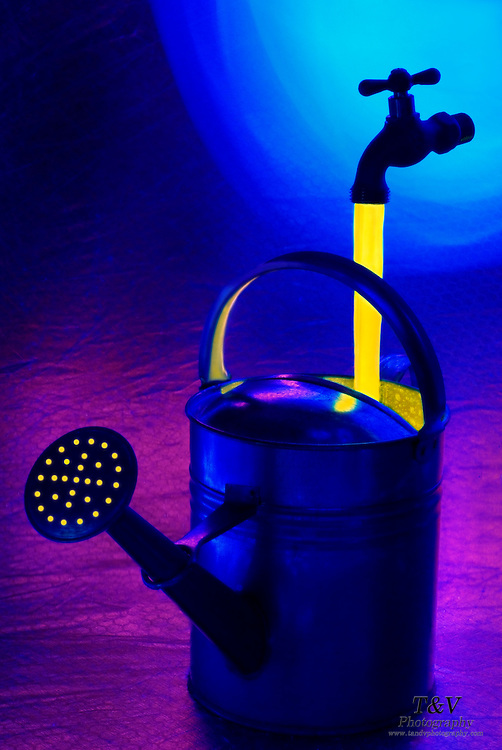 A floating faucet pours glowing yellow fluid into a water can.Black light