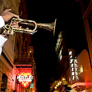 A young African American trumpet player performs big band music on a summer night on Bourban St. in New Orleans, LA.