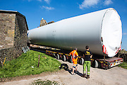 The base of a wind turbine arriving by an exceptional load lorry is guided through the farm buildings at Alvington Court Farm, Forest of Dean. Gloucestershire. The truck has rear steering to guide it through small lanes to arrive at its location ready for construction.