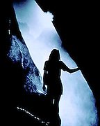 A woman emerges from a cave into the mist of a waterfall in Yosemite National Park, California