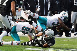 November 28, 2010; Oakland, CA, USA;  Miami Dolphins running back Ricky Williams (34) is tackled by Oakland Raiders cornerback Nnamdi Asomugha (21) during the first quarter at Oakland-Alameda County Coliseum.