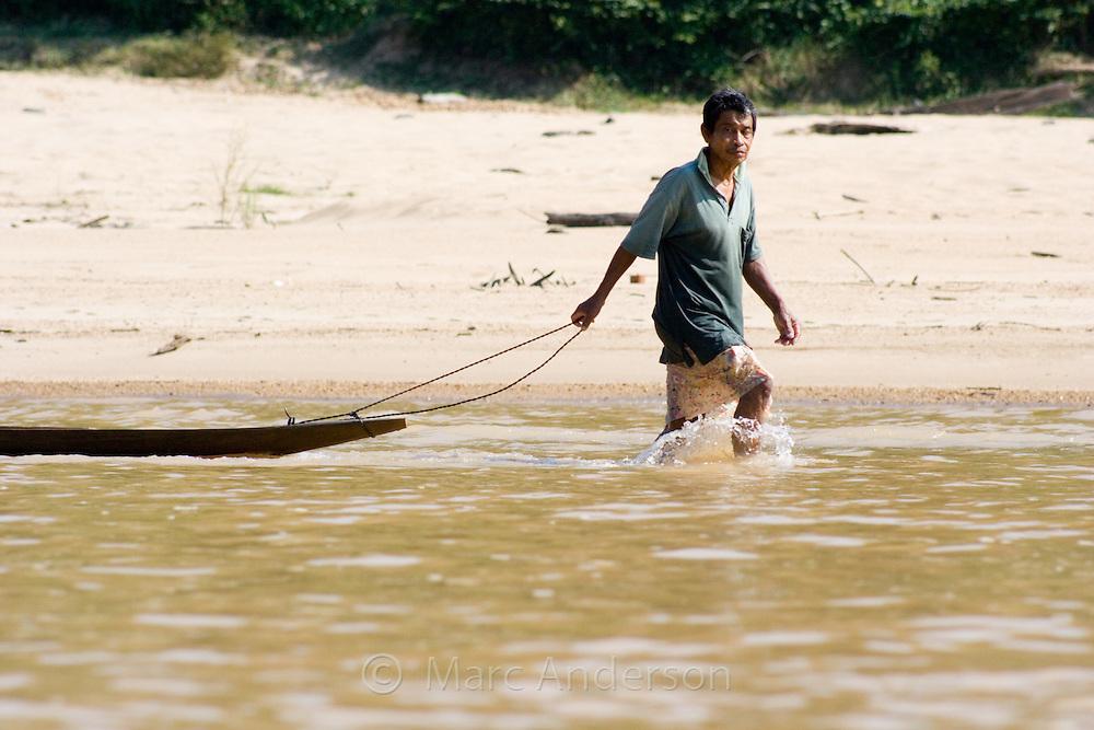 A Malaysian man pulling a boat along a river in Taman Negara National Park, Malaysia..