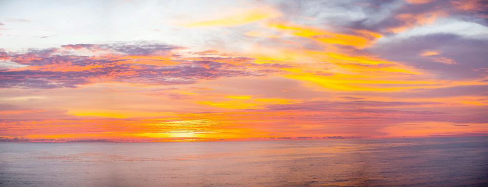 VARKALA, INDIA - 28th September 2019 - Panoramic of vibrant orange sunset over the Arabian Sea at Varkala Cliff Beach, Kerala, Southern India
