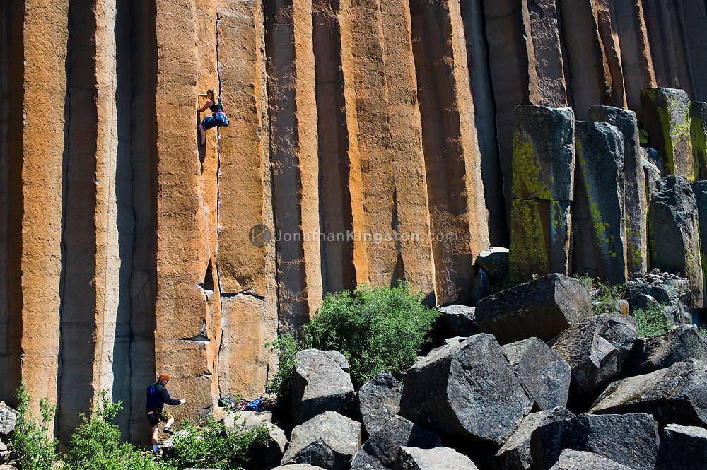 A young woman rock climbing while a mid adult man belays, or holds the safety rope, at Trout Creek, Oregon. (Model Released)
