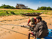 31 MAY 2016 - SIEM REAP, CAMBODIA: Men repair a small speed boat engine along the canal while the Tara sits beached behind them. The Tara is a river freighter and passenger boat assembled in Vietnam, then a French colony, in 1927. Most recently it's used to take tourists on dinner cruises on the Tonle Sap Lake. Because of the drought in Cambodia, the Tara is beached and unable to navigate the nearly empty canals that lead to the Tonle Sap Lake. The boat's owners are repairing and refurbishing it while it's beached and hope that the coming rainy season will flood the canal enough to let the Tara get back to the lake.    PHOTO BY JACK KURTZ