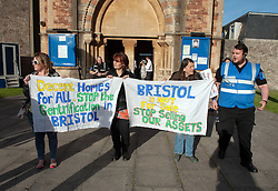 © Licensed to London News Pictures.20/04/2016. Bristol, UK.  Protesters hold  placards at a protest at an auction of council houses held at All Saints Church in Pembroke Road, Clifton, Bristol. Campaigners want the council to stop selling off 14 council homes on 20 April by auction to the private sector. Bristol City Council says the homes are expensive to repair, but some campaigners question whether the costs of repairs are inflated, and also whether the homes will be bought and then relet to the Council for temporary accommodation at higher than normal rents.  A group of residents of St. Paul's and the Inner City are campaigning against the sale. They are working in partnership with The Community Rights Project, The Bristol People's Assembly, and members of the ACORN community union. Photo credit : Simon Chapman/LNP