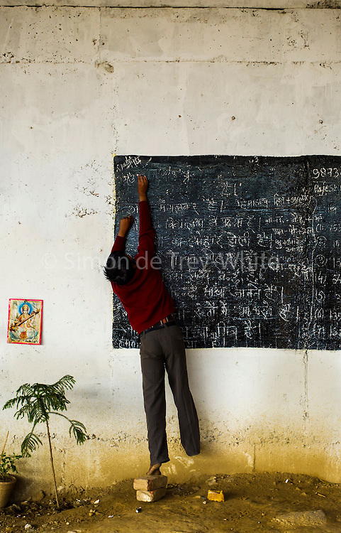 13th March 2014, Shakarpur, New Delhi, India. A boy stretches to write on the top of a blackboard at a makeshift school under a metro bridge, a picture of Saraswati the Hindu Goddess of learning adorns the wall, near the Yamuna Bank Metro station in Shakarpur, New Delhi, India on the 13th March 2014<br /> <br /> Rajesh Kumar Sharma (born 01/02/1970), started this makeshift school in 2011. Six mornings a week he teaches underprivileged children for three hours while his younger brother replaces him at his general store in Shakarpur. His students are children of labourers, rickshaw-pullers and farm workers. This is the 3rd site he has used to teach under privileged children in the city, he began in 1997. <br /> <br /> PHOTOGRAPH BY AND COPYRIGHT OF SIMON DE TREY-WHITE<br /> + 91 98103 99809<br /> email: simon@simondetreywhite.com<br /> photographer in delhi<br /> journalist