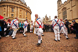 © Licensed to London News Pictures.  01/05/2014. OXFORD, UK. Morris dancers perform in Radcliffe Square in Oxford. Each year at 6am the Magdalen College Choir performs the Hymnus Eucharisticus, from the top of Magdalen Tower, a tradition dating back over 500 years. Around 6,000 students and local residents, some of who have stayed up all night, gather in the street below to listen. Morris dancers then perform around the city. After a number of injuries in previous years a heavy security presence stopped anyone from jumping from the bridge into the Cherwell river. Photo credit: Cliff Hide/LNP