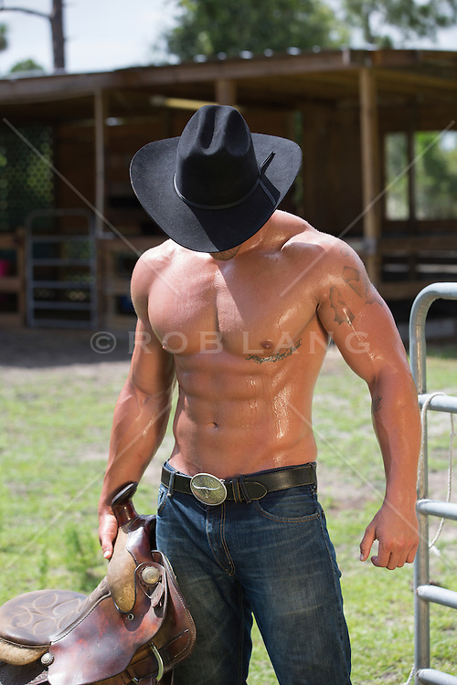 muscular hot cowboy with smooth skin holding a saddle on a working ranch