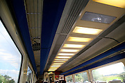 Blurred motion picture of lights and speeding train window travelling inside rail carriage, UK