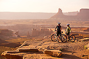 Mountain bikers Brad Barlage and Katie Caviccio take a break and watch  the sun setting  over Canyonlands National Park while mountain biking the White Rim Trail in Southern Utah.