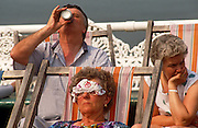 Holidaymakers are seated in deckchairs on the North Pier at Blackpool, England. As a man in the back row drinks deeply from a can and a lady next to him looks intently at life to the right, a more eccentric woman sleeps with a lacy handkerchief stretched across her face, pinned inside her sunglasses. Looking very English with embroidered or printed pattern of flowers. This northern seaside resort in the north-west of England is diverse in its transient holiday population whose behaviour can be routinely odd. Blackpool is the largest resort in the north of England and visited traditionally by working people from industrial towns and cities during the industrial revolution.