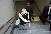 Japan elderly person working cleaning subway stairs