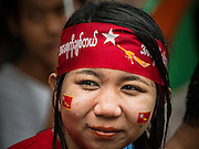 09 NOVEMBER 2015 - YANGON, MYANMAR: A woman sits in the rain at NLD headquarters Monday. Thousands of National League for Democracy (NLD) supporters gathered at NLD headquarters on Shwegondaing Road in central Yangon to celebrate their apparent landslide victory in Myanmar's national elections that took place Sunday. The announcement of official results was delayed repeatedly Monday, but early reports are that the NLD did very well against the incumbent USDP.     PHOTO BY JACK KURTZ