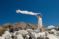 Woman in flowing white gown standing in a magestic landscape making a cloud appear.