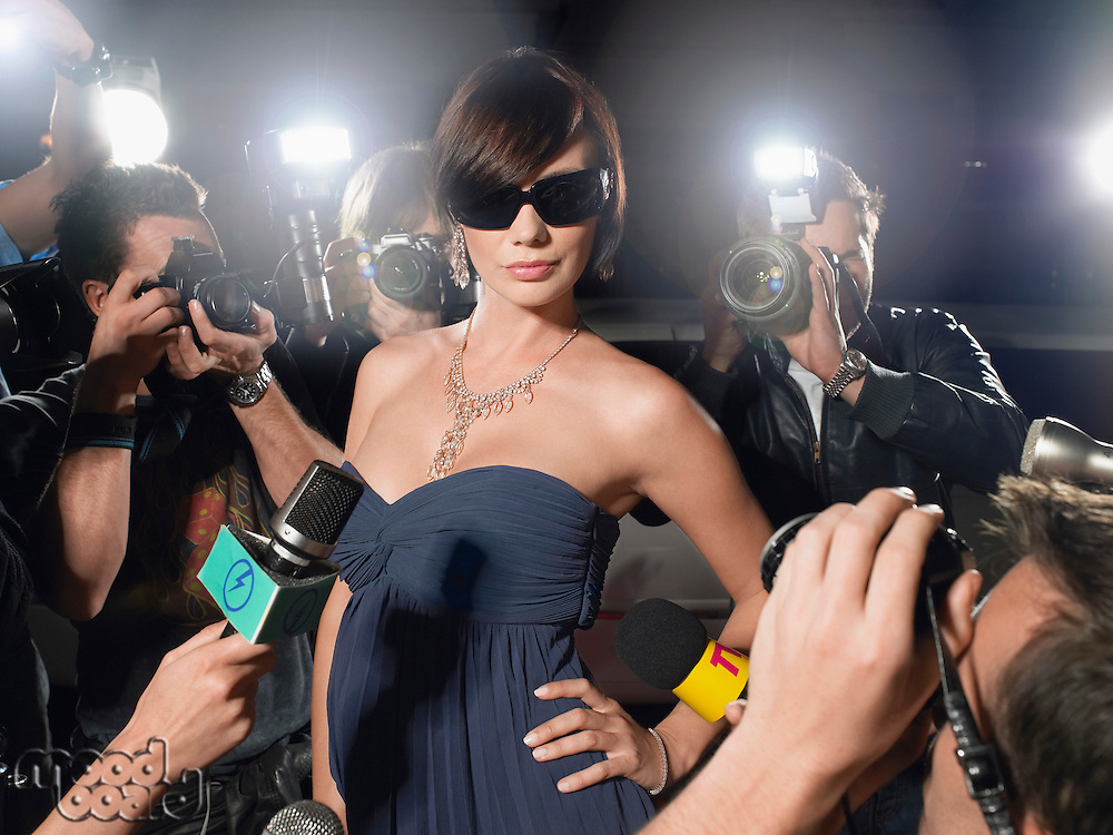 Woman wearing sunglasses posing on red carpet being photographed by paparazzi