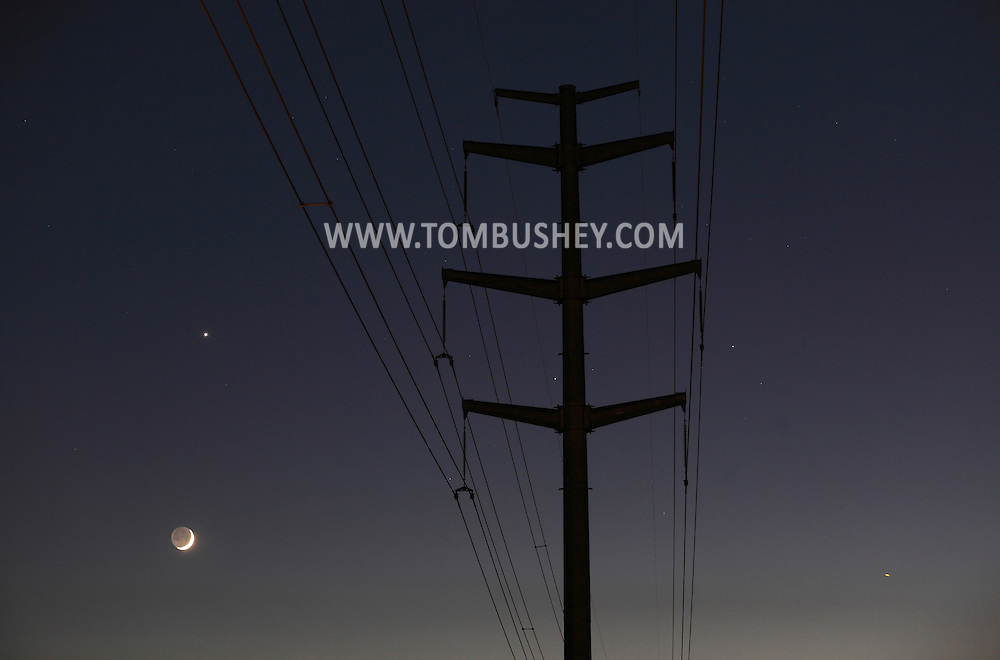 Middletown, New York - A crescent moon and Venus shine behind power lines on June 14, 2010.