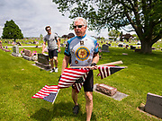 25 MAY 2020 - ROLAND, IOWA: LARRY RITLAND carries American flags as he walks through Roland Cemetery, in Roland, Iowa, a farming community an hour north of Des Moines. Ritland, a Vietnam era veteran, rode his bicycle about 74 miles through central Iowa to honor veterans buried in cemeteries in rural Iowa. In 2020, most public Memorial Day events in Iowa were canceled because of the COVID-19 pandemic, but some families, including the Ritlands, had their own private events. Memorial Day is a federal holiday to honori and mourn the military personnel who have died while serving in the United States Armed Forces. Memorial Day is observed on the last Monday in May.        PHOTO BY JACK KURTZ