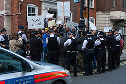 "Mayfair, London, November 28th 2014. A protest against Egypt's leader Al-Sisi descended into moinor scuffles as right wing ""patriots"" from anti-Islamic group Britain First arrived to protest against the presence of Islamist preacher Anjem Choudary, who was recently arrestred as part of an ant-terror operation. Playing patriotic British Music, Britain First accused Muslims of worshiping a ""devil"" and a ""paedophile prophet"". Police had to intervene before hotheads on both sides became violent. PICTURED: Police surround Muslims as they attempt to keep Britain First and Muslim Brotherhood-supporting anti-Sisi protesters separate."