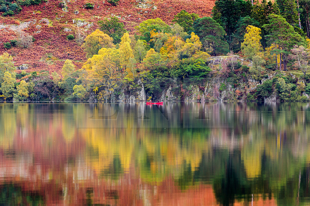 © Licensed to London News Pictures. 15/10/2018. Glenridding UK. Two people paddle a little red canoe across the still water of Ullswater lake near Glenridding this morning in Cumbria. Photo credit: Andrew McCaren/LNP