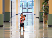 Siblings occupy themselves as staff make preparations for the first day of school at Mading Elementary School, August 20, 2014.