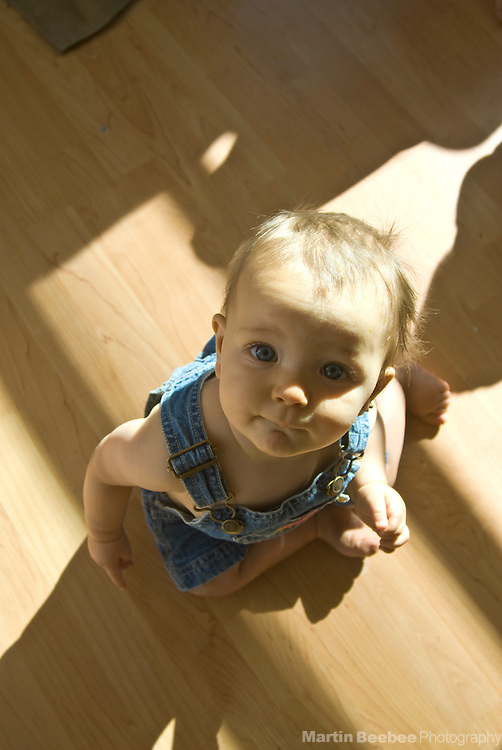 A nine-month-old baby boy looks up from the floor