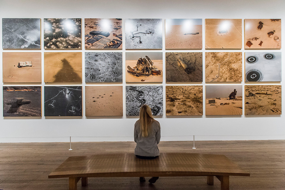 Sophie Ristelhueber's aerial views of the desert landscape of Kuwait after the first Gulf War.  Conflict, Time, Photography, a new exhibition at the Tate Modern - showcasing the unique ways photographers look back at moments of conflict, from the seconds after a bomb is detonated to 100 years after a war has ended. It includes: renowned photographers Don McCullin, Kikuji Kawada and Taryn Simon; Luc Delahaye's large-scale image of the US bombing of Taliban positions in Afghanistan, showing a cloud of smoke rising from the battlefield; Hiromi Tsuchida's large-scale photograph of a watch stopped at the moment the atomic bomb fell on Hiroshima in 1945; The Archive of Modern Conflict's colourful and chaotic new installation, bringing together war-related images and objects from around the world and across the past 100 years; and Chloe Dewe Mathews's haunting landscapes photographed at dawn, showing the places where British soldiers were executed for desertion and cowardice in the First World War. The show runs from 26 November 2014 – 15 March 2015. Tate Modern, London, UK 25 Nov 2014.