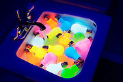Colorful lighbulbs glowing in a sink.Black light