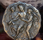 An ancient Greek coin or medal with a depiction of three muses. Photographed in Athens, Greece