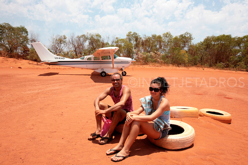 Father and daughter sitting on rubber tyres, waiting for the plane to leave, at the landing strip at Cape Leveque at Kooljaman at The Dampier Peninsula, North of Broome. Published in Korean Air Inflight Magazine 'Morning Calm', April 2013
