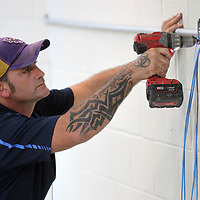 Paul Landry, an installer with City Tele Coin in Bossier City, Louisiana, secures an electrical box to the wall during the installation of two monitor systems inside the A Pod cell at the Lee County Jail on Tuesday.