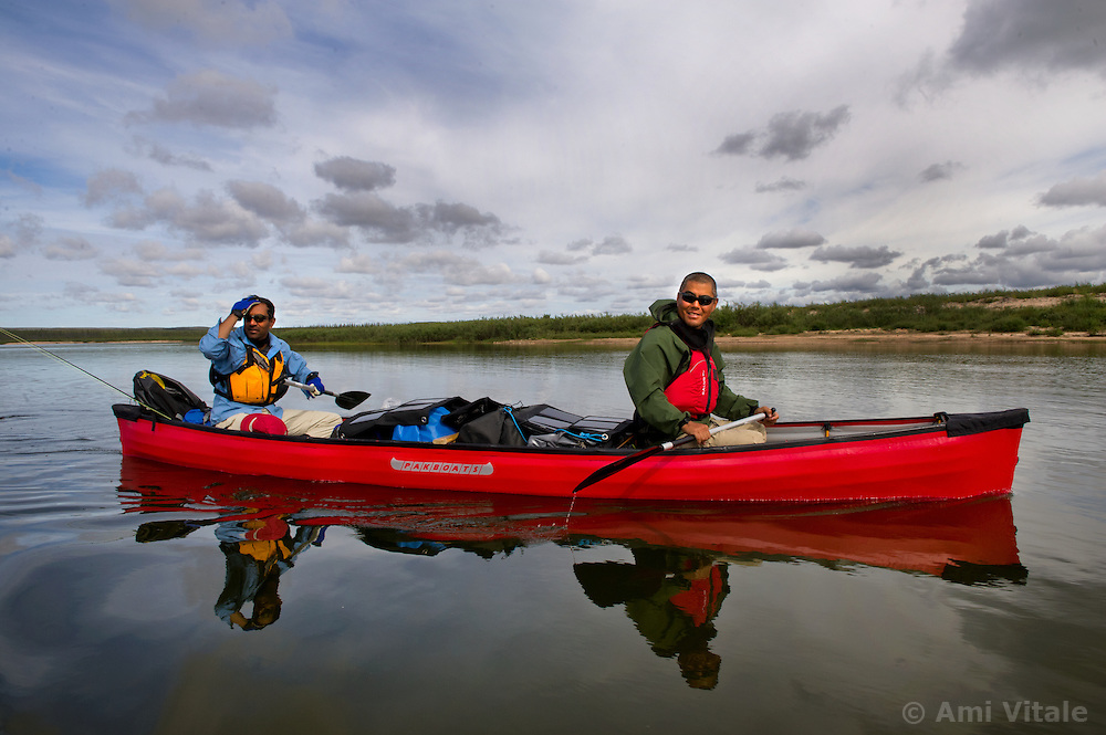 Richard Jeo, a scientist with the Nature Conservancy,  right, and Sanjayan Muttulingam paddle with solar panels to chatge up their sat phone and computer along the Thelon river In the middle of the largest and most remote game sanctuary in North America, in the Northwest Territories, just south of the Arctic Circle. Its fate now hangs in the balance, protected on paper, but with little management, no money, and no voice for the Dene, its most ardent advocate for protection, while mining (for diamonds, gold, and uranium) threats, buoyed by recent prices, loom.  Dene youth have rarely been deep into the Thelon, yet the caribou is still their life blood, reverentially important.  These Dene are amongst the last hunter/gatherers in the Northern Hemisphere.   (Photo by Ami vitale)