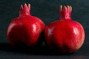Two ripe pomegranates on black background