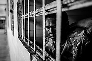 BARQUISIMETO, VENEZUELA - AUGUST 24, 2016: Margarita Silva, a paranoid schizophrenic, looks out of the window of her solitary confinement cell, where she was being held because two days earlier she attacked another patient in the middle of the night, and bit off her nose and ate it. The nursing staff said she had been without two of the medicines she needs to take to control her disorder when the attack occurred, and that they believe that it is unlikely that she would have acted out if she had been medicated, or if she had been under the regular care of a psychiatrist. The economic crisis that has left Venezuela with little hard currency has also severely affected its public health system, crippling hospitals like El Pampero Psychiatric Hospital by leaving it without the resources it needs to take care of patients living there, the majority of whom have been abandoned by their families and rely completely on the state to meet their basic needs. The hospital has not employed a psychiatrist for over two years. Drugs used to combat bipolar disorder, epilepsy, schizoaffective disorder and chronic anxiety are now in short supply, as are numerous sedatives and tranquilizers needed to care for patients. Members of the nursing staff debate daily which patients are the most unstable, to decide which patients will receive pills and which will go without. When a patient loses control, often the only thing they can do is restrain them, or lock them in an isolation cell to prevent them from hurting themselves, other patients and members of the staff.  PHOTO: Meridith Kohut for The New York Times