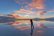 South America, Andes, Altiplano, Bolivia, Salar de Uyuni, woman taking pictures at sunset