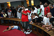 Rev. Stephen W. Pogue, the Pastor, embracing an exited  devotee after the blessing, while a young woman (left) has fainted on the floor in ecstasy, after having being filled by the Holy Spirit, at the Hip Hop Church in Harlem, New York, NY., on Thursday, July 21, 2006. Other devotees are waiting in line. A new growing phenomenon in the United States, and in particular in its most multiethnic city, New York, the Hip Hop Church is the meeting point between Hip Hop and Christianity, a place where ëGodí is worshipped not according to religious dogmatisms and rules, but where the ëHoly Spirití is celebrated by the community through young, unique, passionate Hip Hop lyrics. Its mission is to present the Christian Gospel in a setting that appeals to both, those individuals who are confessed Christians, as well as those who are not regularly attending traditional Services, while helping many youngsters from underprivileged neighbourhoods to feel part of a community, to make them feel loved and to help them not to give up when problems arise. The Hip Hop Church is not only forward-thinking but it also has an important impact where life at times can be difficult and deceiving, and where young people can be easily influenced for the worst purposes. At the Hip Hop Church, members are encouraged to sing, dance and express themselves in any way that the ëSpirit of Godí moves them. Honours to students who have overcome adversity, community leaders, church leaders and some of the unsung pioneers of Hip Hop are common at this Church. Here, Hip Hop is the culture, while Jesus is the centre. Services are being mainly in Harlem, where many African Americans live; although the Hip Hop Church is not exclusive and people from any ethnic group are happily accepted and involved with as much enthusiasm. Rev. Ferguson, one of its pioneer founders, has developed ëHip-Hop Homileticsí, a preaching and worship technique designed to reach the children in their language and highlight their sensibil