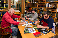 With a collection of dyed bird feathers, ostrich feathers, dyed deer tail and other items Captain Dennis Caldwell teaches Diane and Dan Tarullo the art of Fly Tying at the Gilford Public Library on Thursday evening.   (Karen Bobotas/for the Laconia Daily Sun)