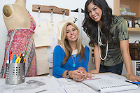 Portrait of female fashion designers at desk