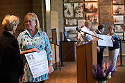 Ruth Pratt of the Coeur d'Alene Public Library Foundation stands with a check for $22,625 from the Women's Gift Alliance received at the Public Library on Thursday as Howard Martinson, right, of Fresh Start Inc. holds his check of equal value during the WGA's 6th annual grant presentation to local non-profit groups.
