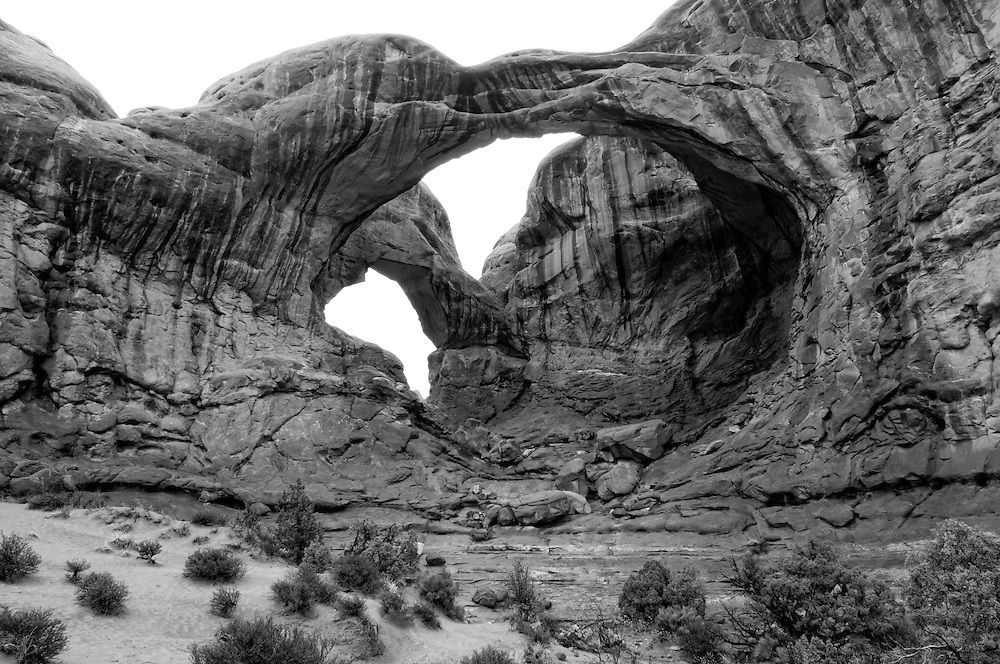Double Arch is found in Arches National Park in Eastern Utah and is part of the amazing red alien sandstone landscape that is called the Moab Desert. This area has the largest number of natural stone arches than anywhere else in the world, but what makes this rock formation so unique is that they were both eroded from the very same piece of stone. Most arches are formed from water erosion flowing either within or from the sides of the rock over the millennia, but these two arches were formed from water eroding from the top of the stone, downwards. For this reason they are called pothole arches. Because this photograph was made at the beginning of a sudden storm, you can see the rainwater running down the rock from the top of the arch, and this is the very process that carved these arches to begin with, and that will also eventually one day cause this magnificent national treasure to collapse.
