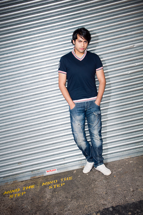 Young asian hollyoaks actor leaning on a steel corigated door.