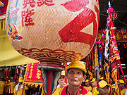 "23 JUNE 2015 - MAHACHAI, SAMUT SAKHON, THAILAND: An attendant carries a Chinese lantern in the City Pillar Shrine Procession in Mahachai. The Chaopho Lak Mueang Procession (City Pillar Shrine Procession) is a religious festival that takes place in June in front of city hall in Mahachai. The ""Chaopho Lak Mueang"" is  placed on a fishing boat and taken across the Tha Chin River from Talat Maha Chai to Tha Chalom in the area of Wat Suwannaram and then paraded through the community before returning to the temple in Mahachai.   PHOTO BY JACK KURTZ"
