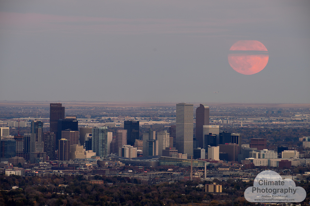 Supermoon over downtown Denver. The last time the #moon was this close to Earth was 1948, and the next time will be November 25, 2034.  This supermoon (named that by an astrologist back in the '70's- very unscientific), combined with atmospheric optic influences such as pollution, Rayleigh scattering (sunset), and the magnifying effect of the atmosphere near the horizon, combined with the distance-compression effect of a 500mm camera lens, all make the moon in this image appear very large.  Astronomy combined with optics is quite interesting!  Go outside and look at the moon tonight, in the morning, and tomorrow night- you won't see this size and brightness again for a while, and there aren't many clouds in America tonight.<br />